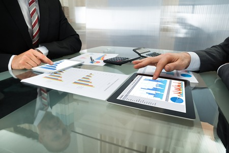 40751667 - close-up of two businessman analyzing graph on digital tablet